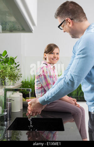 Smiling girl looking at father washing hands in kitchen - Stock Photo