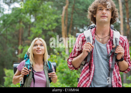 Young hiking couple looking away in forest - Stock Photo