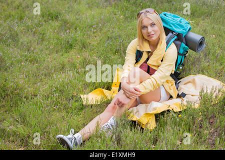 Full length of thoughtful female hiker sitting on grass - Stock Photo