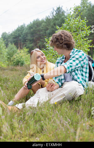 Male hiker pouring coffee for woman while relaxing in field - Stock Photo