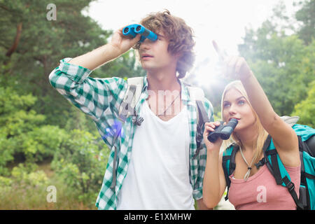 Male hiker using binoculars while woman showing him something in forest - Stock Photo