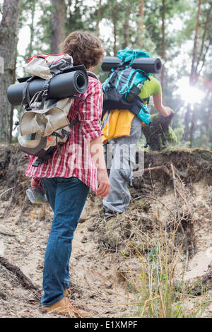 Rear view of man watching female hiker climbing cliff in forest - Stock Photo