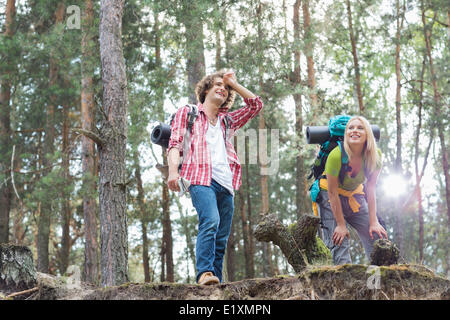 Tired young hiking couple taking a break in forest - Stock Photo