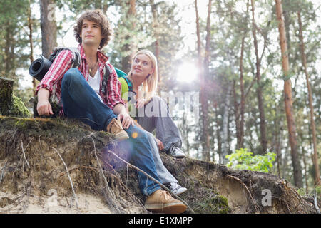 Young hiking couple sitting on edge of cliff in forest - Stock Photo