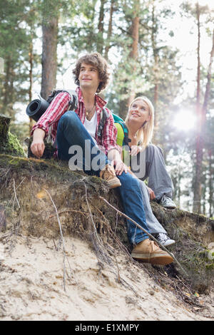Full length of hiking couple sitting on edge of cliff in forest - Stock Photo