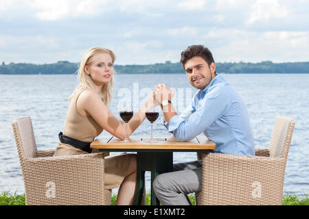 Side view portrait of young couple holding hands at outdoor restaurant by lake - Stock Photo