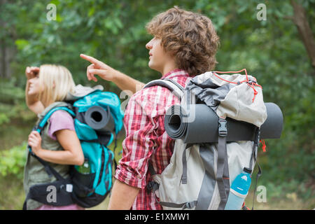 Male backpacker showing something to woman in forest - Stock Photo
