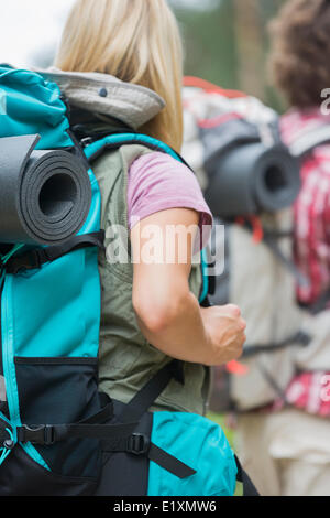Rear view of female hiker carrying backpack with man in background outdoors - Stock Photo