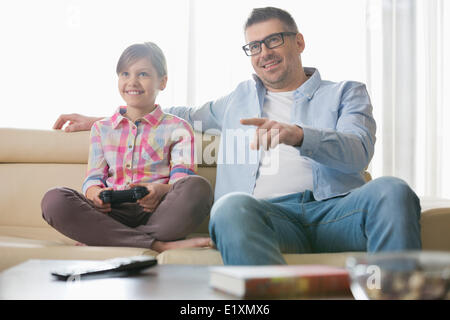 Happy father and daughter playing video game in living room - Stock Photo