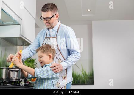 Father and son preparing spaghetti in kitchen
