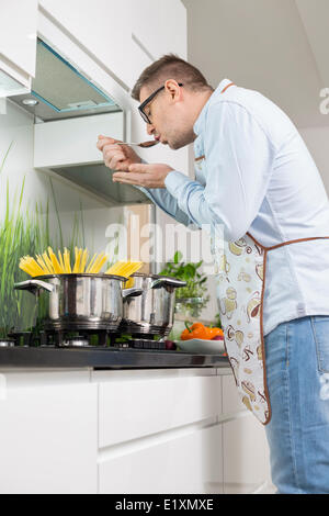 Mid-adult man tasting food while cooking in kitchen - Stock Photo