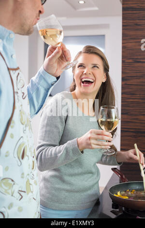 Cheerful couple having wine while cooking in kitchen - Stock Photo