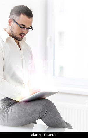 Young businessman using digital tablet in office - Stock Photo
