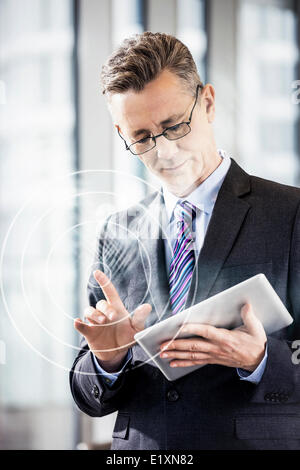 Middle aged businessman using digital tablet in office - Stock Photo