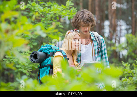 Hiking couple reading map together in forest - Stock Photo