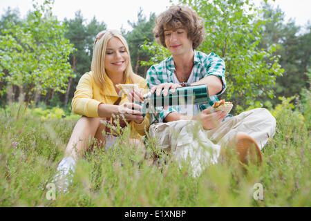 Young male hiker pouring coffee for woman while relaxing in field - Stock Photo