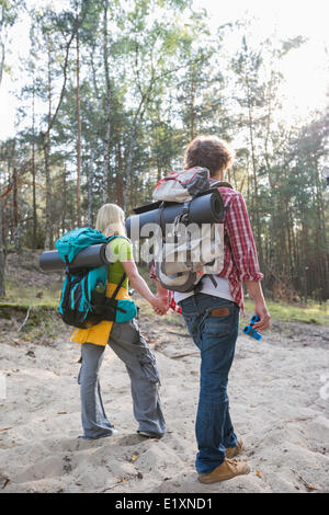 Rear view of hiking couple with backpacks walking in forest - Stock Photo
