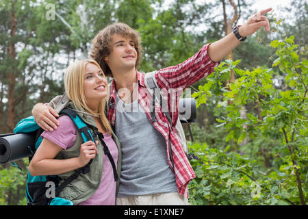 Young male hiker showing something to woman in forest - Stock Photo