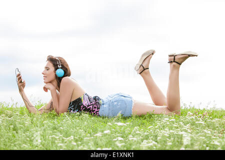 Profile shot of woman listening to music through cell phone using headphones while lying on grass against sky - Stock Photo
