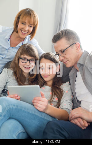 Family using digital tablet together in living room - Stock Photo