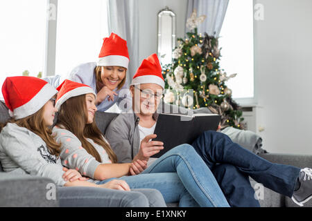 Family of four reading book in living room during Christmas - Stock Photo