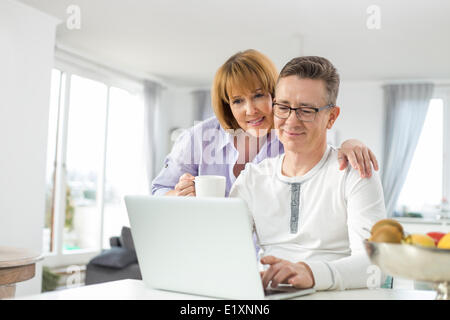 Loving couple using laptop together at home - Stock Photo