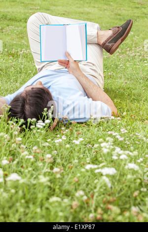 Full length of young man holding book while lying on grass in park - Stock Photo