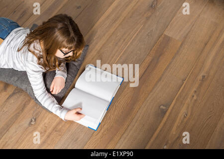 High angle view of teenage girl reading book on floor at home - Stock Photo