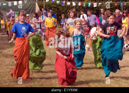Youngsters competing in a sack race at a village summer fair, Dockenfield, UK. - Stock Photo