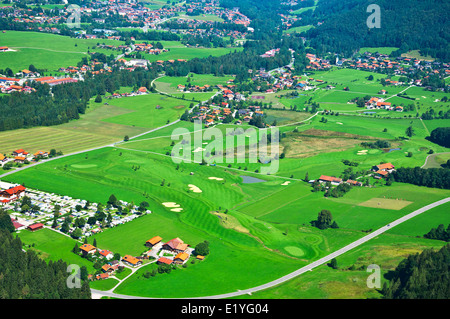 Birds view of a rural landscape in the alps with golf course - Stock Photo
