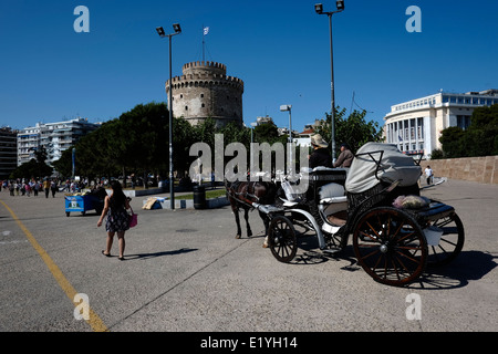 A horse-drawn carriages waiting for customers near the White Tower to stroll on the pier of Thessaloniki - Stock Photo