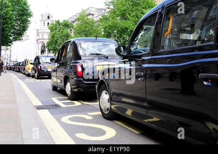 Black cab drivers block a road in central London. - Stock Photo
