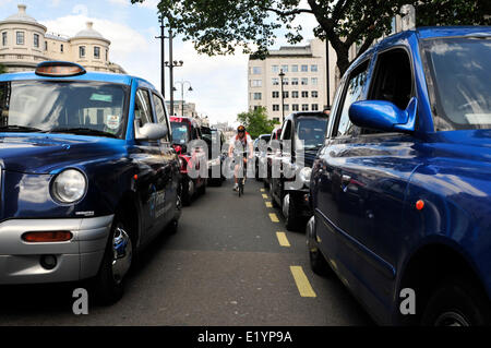 A man cycles between black cabs, central London, UK - Stock Photo