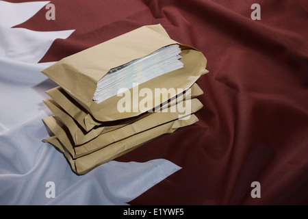 Qatar flag with brown envelopes full of money - Stock Photo