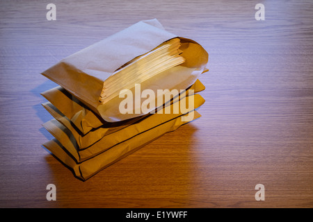 Brown envelopes full of money - Stock Photo