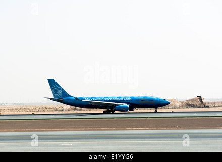 An Etihad airways airplane on the runway at the airport in Abu Dhabi. - Stock Photo
