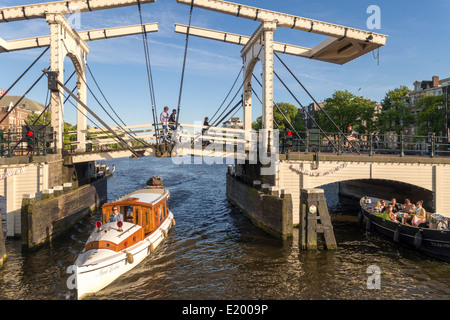 Amsterdam small vintage private VIP canal cruise boat with Magere Brug, Skinny Bridge on the Amstel River - Stock Photo