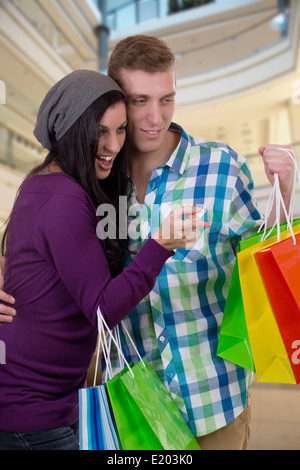 A young couple is finding something while shopping in a mall - Stock Photo