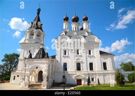white Church with black domes in women's monastery in sunny day - Stock Photo