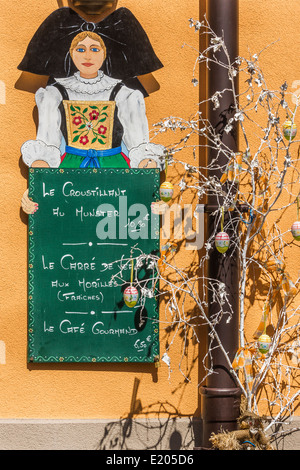 sign of a restaurant showing a young woman in traditional alsatian garb and advertising alsatian culinary specialities - Stock Photo