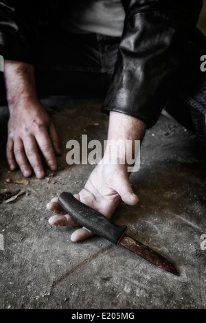 man's hands with an old, rusty knife - Stock Photo