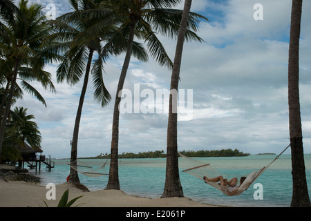Aitutaki. Cook Island. Polynesia. South Pacific Ocean. Two tourists resting in a hammock in the beach of the Hotel - Stock Photo