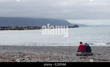 Couple on a pebble beach by the Pacific Ocean near Crescent City, northern California. - Stock Photo