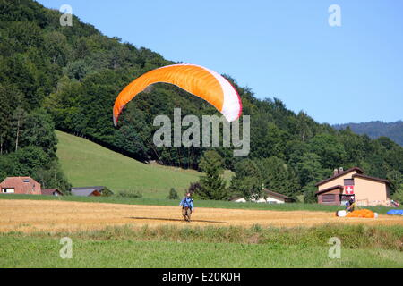 Paraglider landing in a field - Stock Photo