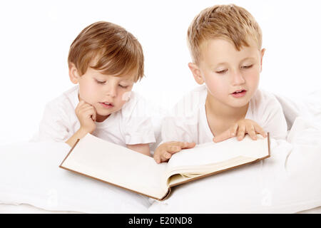 Two little boys read the book in the bed - Stock Photo
