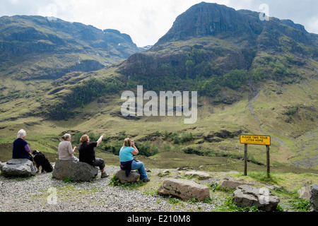 Four women looking at view from Glen Coe Pass layby to Gearr Aonach ridge in Bidean nam Bian mountain massif. Glencoe - Stock Photo