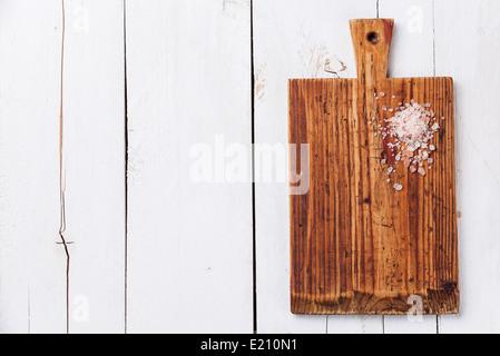 Pink salt on Kitchen Cutting board on white wooden texture background - Stock Photo