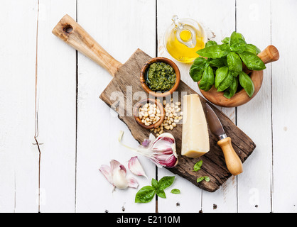 Ingredients for Preparing pesto in mortar on white wooden background - Stock Photo