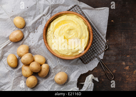 Mashed potatoes and raw potatoes on dark wooden background - Stock Photo