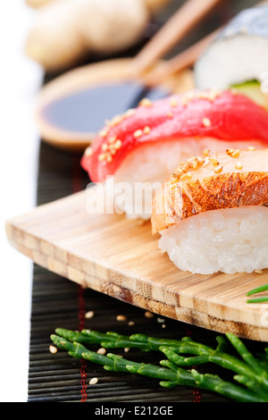 set of japanese sushi with chopsticks and soy sause over white rice - Stock Photo